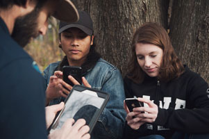 Youth outside in nature with mobile devices